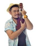 愉快的亚洲人拥抱尤克里里琴孤立背景 免版税图库摄影