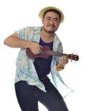 愉快的亚洲人跳舞和演奏尤克里里琴孤立背景 免版税库存照片