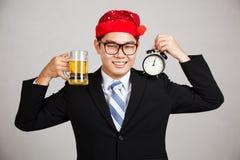 愉快的亚洲商人用啤酒和时钟在午夜 免版税库存照片