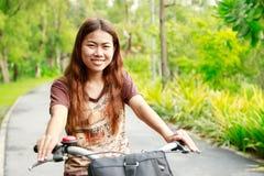 年轻愉快的亚洲女孩骑马自行车在公园放松 库存图片