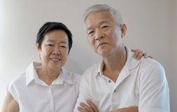 愉快的亚洲资深夫妇白色背景爱和拥抱 免版税图库摄影