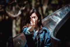 愉快的亚洲青年少年两个手指和听的音乐 图库摄影