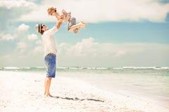 愉快的享受海滩时间的父亲和儿子在夏天 库存照片
