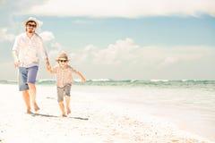 愉快的享受海滩时间的父亲和儿子在夏天 库存图片