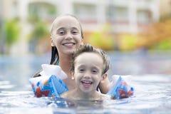 愉快的享用在游泳池的女孩和男孩 免版税库存照片