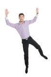 愉快的人。跳跃用他的手的愉快的年轻人反对白色 库存照片