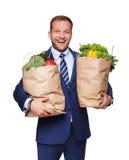 愉快的人举行袋子用健康食物,杂货买家被隔绝 免版税库存图片