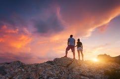 愉快的人剪影山的反对五颜六色的天空 库存照片