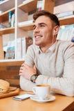 年轻愉快的人听的音乐和饮用的咖啡 库存图片