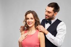 愉快的人在他的女朋友上把项链放 免版税库存图片