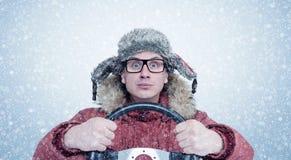 愉快的人在冬天穿衣与方向盘,雪飞雪 概念汽车司机 免版税图库摄影