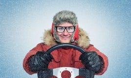 愉快的人在冬天穿衣与方向盘,雪飞雪 概念汽车司机 库存照片