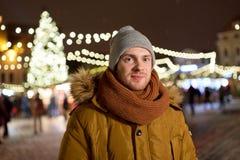 愉快的人在冬天穿衣在圣诞节市场上 免版税图库摄影