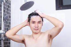 愉快的人在卫生间里采取一根阵雨和洗涤的头发 免版税库存照片