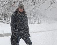 愉快的人在多雪的公园 免版税库存图片