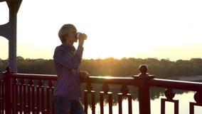 愉快的人在Slo Mo喝咖啡并且享受在一座桥梁的日落 股票录像