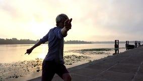愉快的人在Slo Mo转过来并且跳舞在一个美丽如画的河岸在日落 股票视频