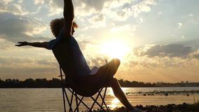 愉快的人并且延长坐河岸在精采日落在slo mo 股票录像