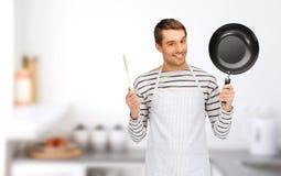 愉快的人或厨师围裙的与平底锅和匙子 免版税图库摄影