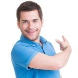 年轻愉快的人显示一个手指。 免版税库存照片