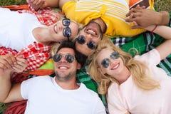 愉快的人民编组躺下在野餐毯子的年轻朋友室外 免版税库存照片