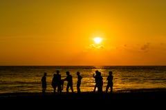 年轻愉快的人民enjoing的日落剪影  免版税图库摄影