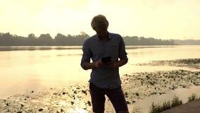 愉快的人看他的智能手机并且对Dnipro微笑户外 影视素材