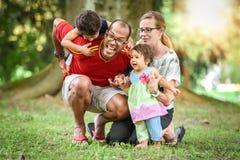 愉快的人种间家庭是活跃的一天在公园 库存图片