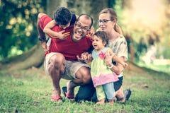 愉快的人种间家庭是活跃的一天在公园 免版税库存图片