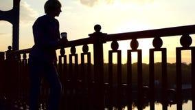 愉快的人站立与一杯纸咖啡并且享用象在日落 股票录像