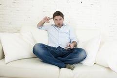 年轻愉快的人观看的电视怀疑地和震动面孔表示 库存照片