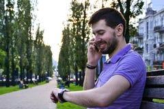 愉快的人谈话在看手表的电话户外 免版税库存图片