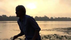 愉快的人跳舞并且拍在河岸的手在精采日落在Slo Mo 股票视频