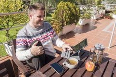 愉快的人食用与技术的早餐在庭院 免版税库存照片