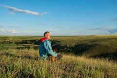 愉快的人,旅客坐与在一个绿色大草原中的一条小狗 库存图片