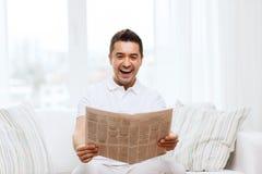 愉快的人读书报纸和嘲笑在家 免版税图库摄影