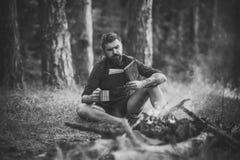 愉快的人 有书和杯子的行家远足者在篝火在森林里 库存图片