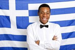 愉快的人画象有胳膊的横渡了反对希腊旗子 免版税库存照片