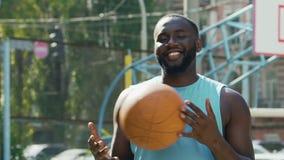 愉快的从一只手的人投掷的球到另一个,感到骄傲为streetball胜利 股票录像