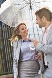 愉快的企业夫妇交谈在伞下户外 免版税图库摄影