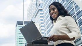 愉快的企业非洲妇女画象使用计算机膝上型计算机 免版税库存图片