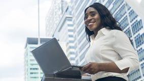 愉快的企业非洲妇女画象使用计算机膝上型计算机  库存图片