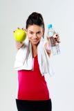 年轻愉快的体育妇女用苹果和瓶水 库存照片