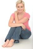 愉快的体贴的轻松的自然少妇坐地板微笑 免版税库存照片