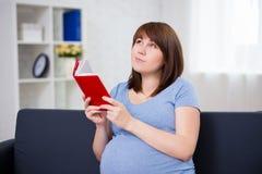 愉快的作的孕妇阅读书在家 免版税库存照片