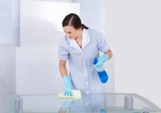 愉快的佣人清洗的玻璃桌 免版税库存照片