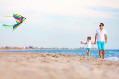 愉快的使用与在夏天海滩的风筝的父亲和儿子 免版税库存照片