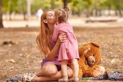 愉快的使用与女用连杉衬裤的妈妈和逗人喜爱的女儿涉及公园背景 长毛绒戏弄概念 免版税图库摄影