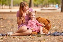 愉快的使用与女用连杉衬裤的妈妈和逗人喜爱的女儿涉及公园背景 长毛绒戏弄概念 库存图片