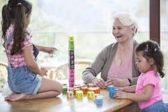 愉快的使用与字母表块的祖母和孙女在桌上 免版税库存照片